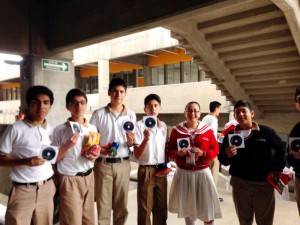 "Middle school students that attended an astronomy lecture at the Universidad de Monterrey during the ""Semana Nacional de la Ciencia y Tecnología"" (National Science and Technology Week) in October 2015 show their ""Un Paseo por el Cielo"" CD ROMs."